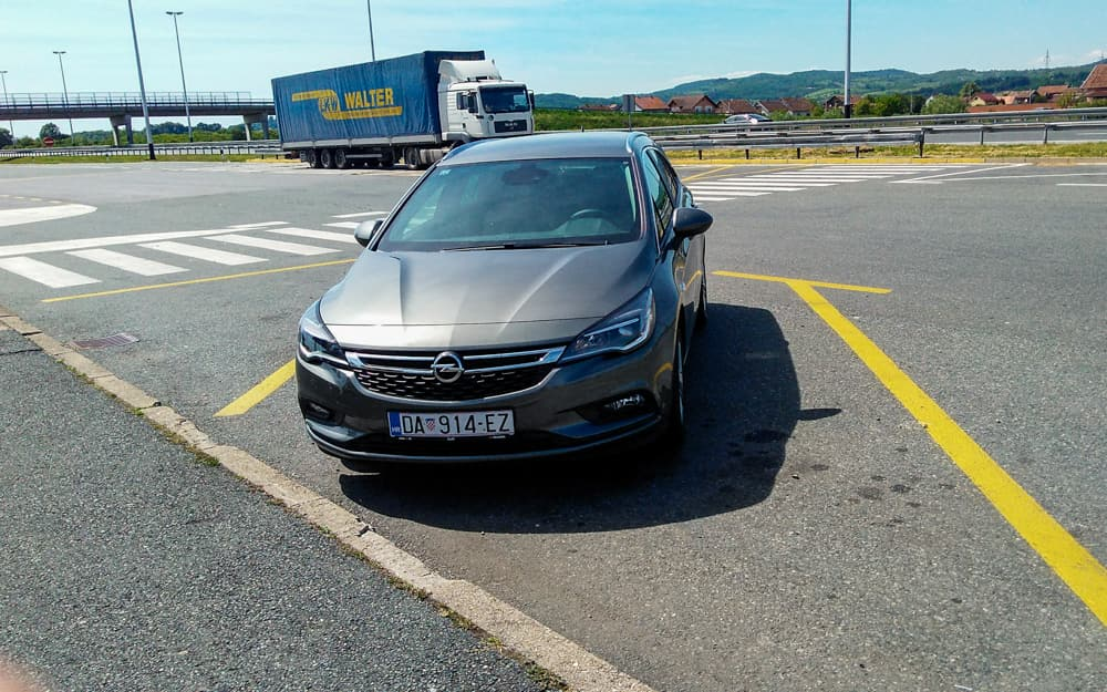 Roteiro Bálcãs: Carro Opel grafite alugado na Croácia, em uma viagem para os Bálticos. O carro está estacionando em uma rodovia da Croácia.