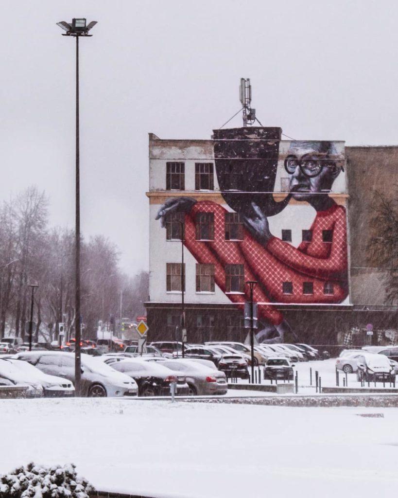 Paisagem de Inverno em Kaunas, na Lituânia. Com o mural Wise Old Man ao fundo, símbolo da street art da cidade.