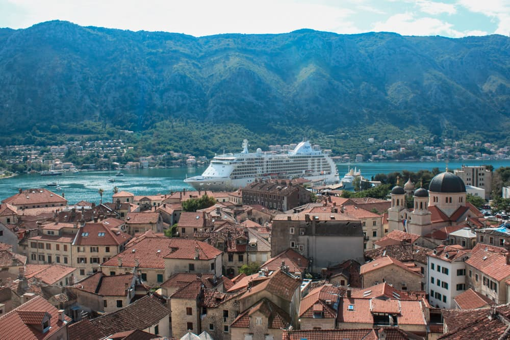 Vista da cidade de Kotor em cima da muralha, em um dia de sol com telhadinhos laranjas e um navio atracado em sua baía.