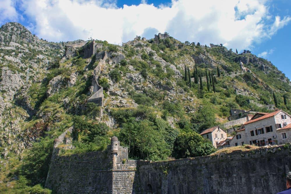 Entrada para cidade antiga pelo Portão Norte, com vista para parte da muralha na montanha.