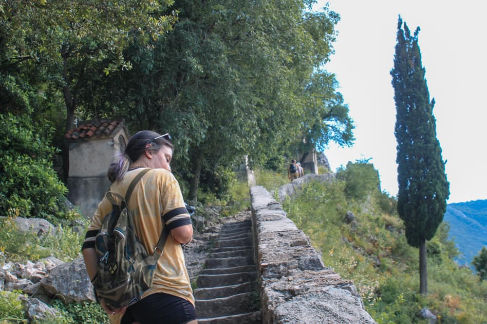 Marjorie subido as escadas de pedra da muralha de Kotor durante o dia.