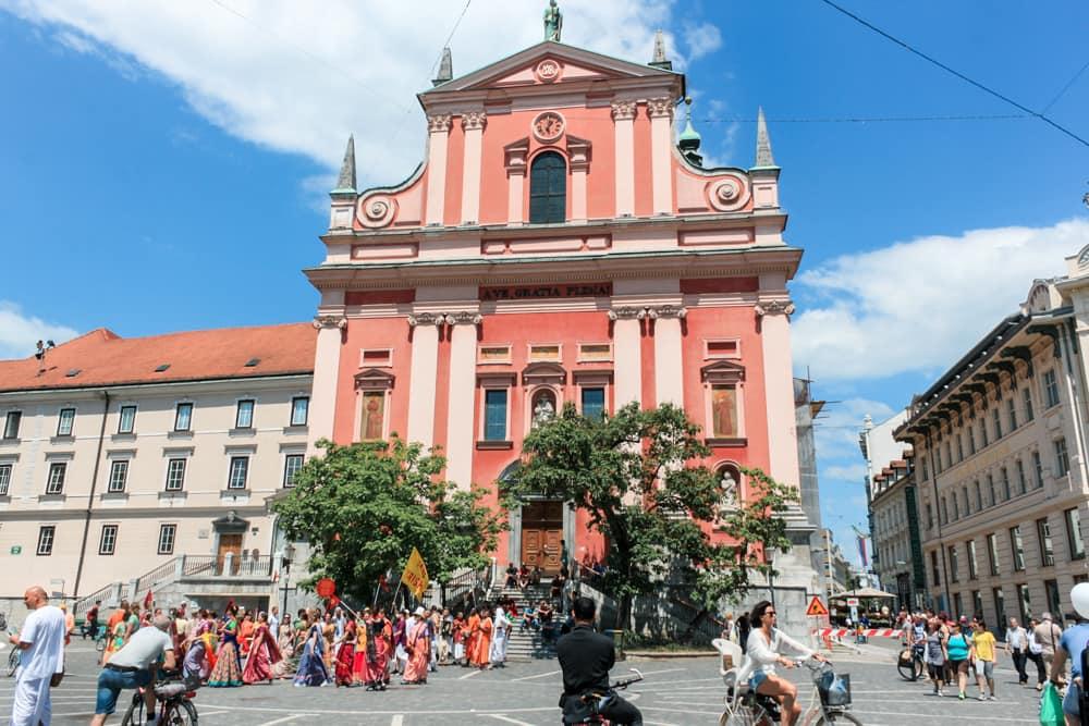 Roteiro Bálcãs: Igreja da Assunção, a igreja rosa no centro de Ljubljana, em um dia ensolarado. Na foto um grupo de Hare Krishnas passam em caminhada na frente.