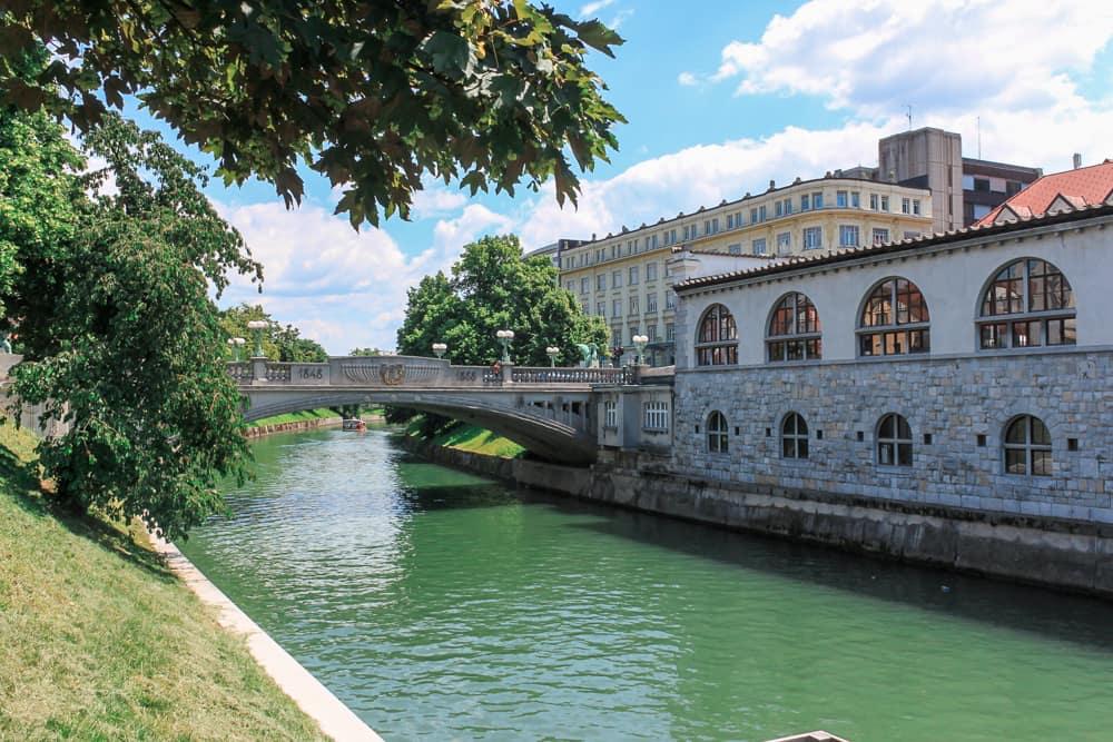 Roteiro Bálcãs: Dia ensolarado e vista para o Rio Ljubljanica no centro de Ljubljana, com a Ponte do Dragão o atravessando.