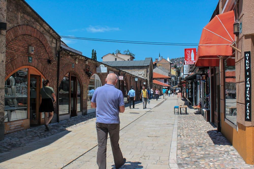 Passeio em um dia bem ensolarado por uma das ruas de Baščaršija, um dos centros mais antigos de comércio, restaurantes e cafés de Sarajevo.