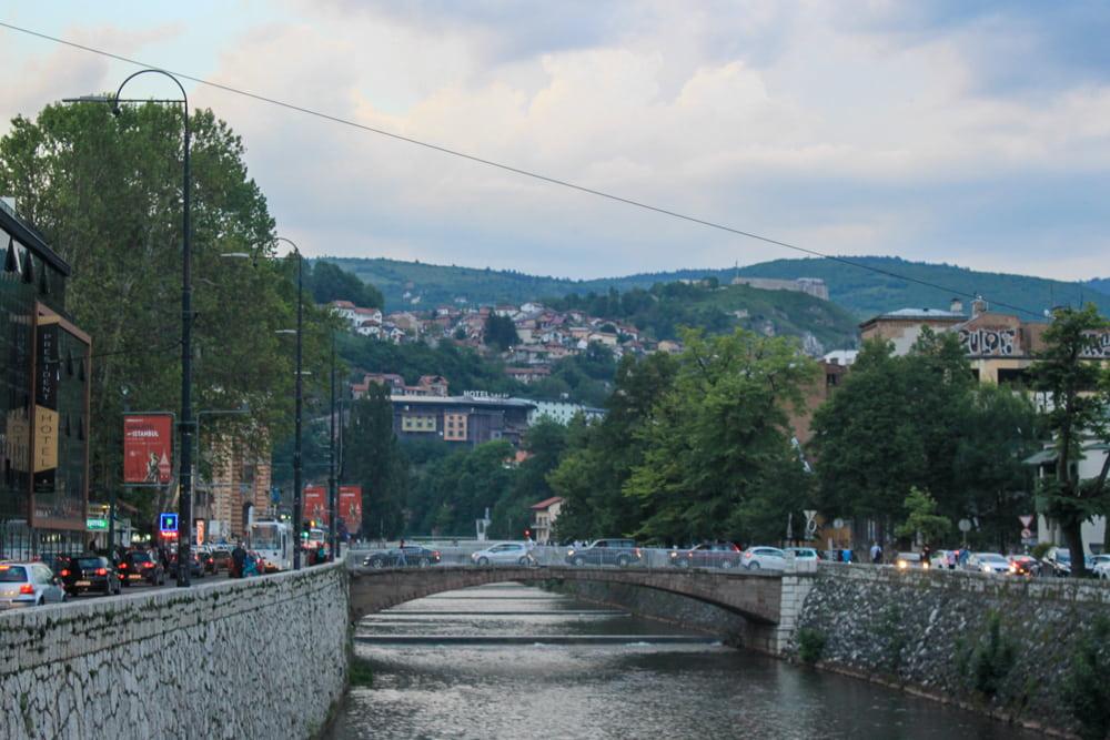 Vista para o rio Miljacka e uma das pontes que o corta com carros passando na rua no final da tarde.