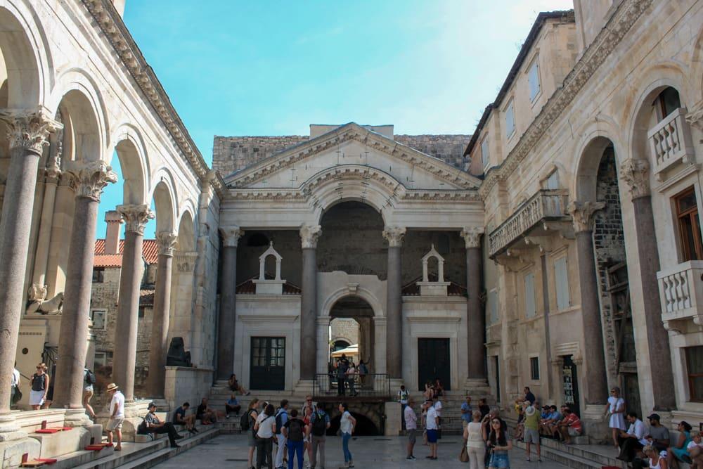 Roteiro Bálcãs: Palácio Diocleciano da cidade de Split, que chama a atenção com sua construção enorme do Império Romano. Muitas pessoas sentadas conversando e muitas outras tirando foto.