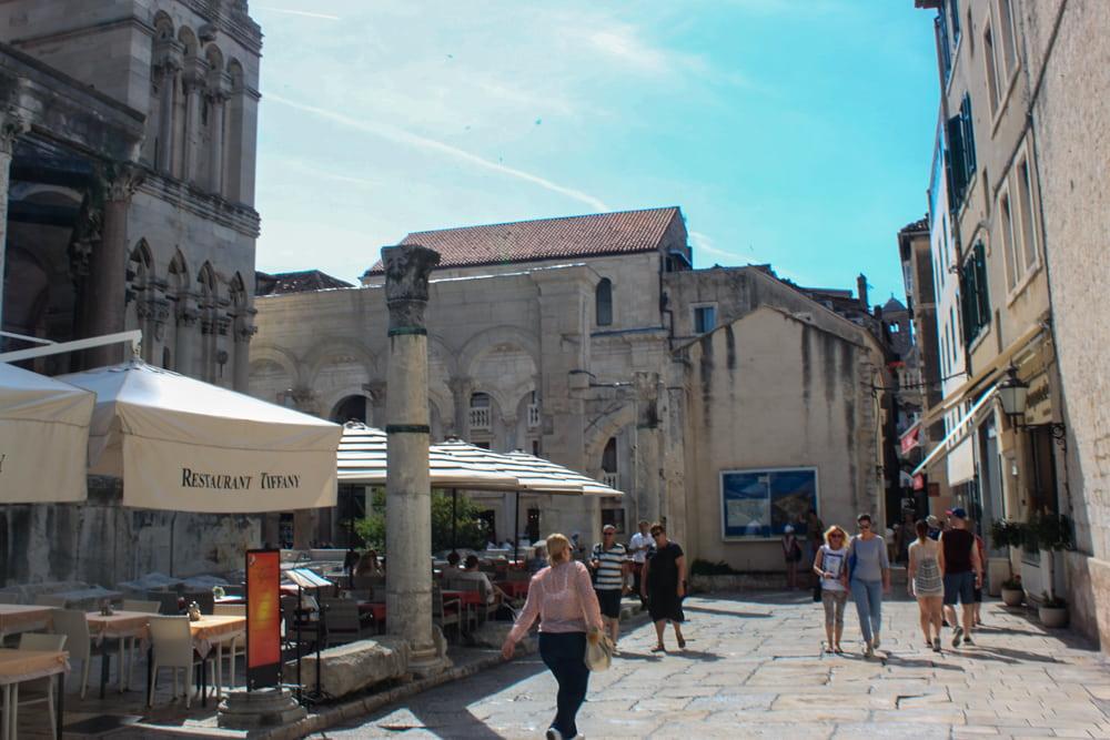 Restaurantes e algumas outras vendinhas dentro do Palácio Diocleciano, em Split, com pessoas passeando pelas ruas de pedra no sol.