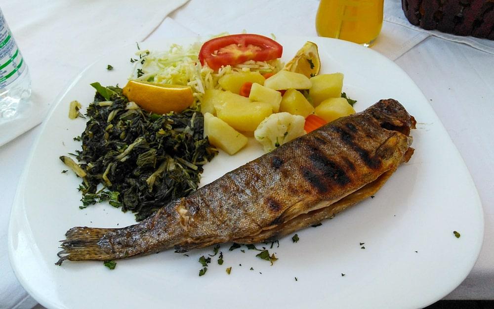 Truta servida com acompanhamentos em restaurante na cidade de Blagaj.