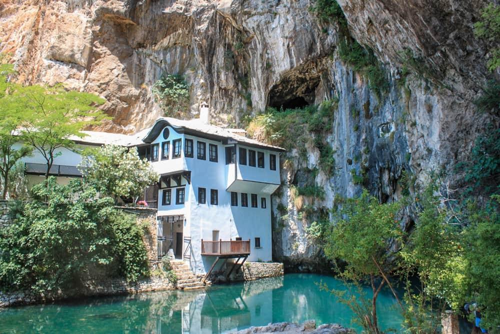 Roteiro Bálcãs: Templo de Blagaj encravado na rocha com um lago de água extremamente azul aos seus pés.