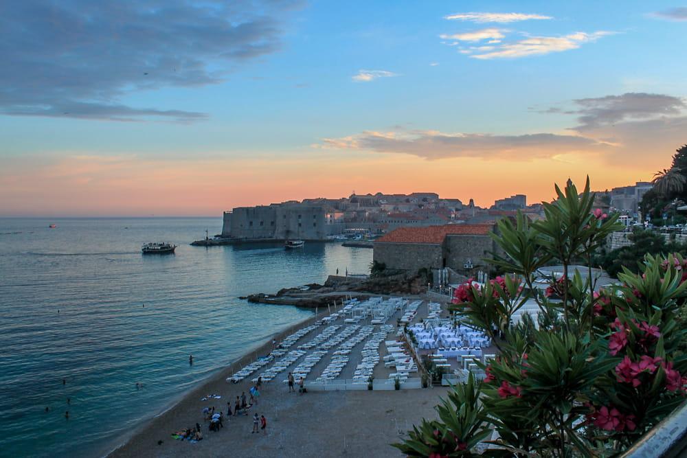 Roteiro Bálcãs: Pôr do Sol da praia de Banje, em Dubrovnik. Ao fundo, com o sol se pondo, está a cidade amuralhada.