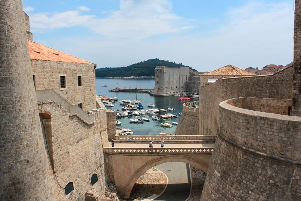 Roteiro Bálcãs: Muralhas de Dubrovnik com o Mar Adriático e a ilha de Lokrum ao fundo. Barcos estão aportados próximo às muralhas.