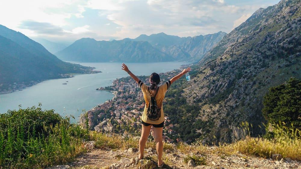 Roteiro Bálcãs: Vista dos fiordes de Montenegro e da cidade de Kotor com as montanhas que a circundam, no topo da Muralha e a Marjorie com os braços para cima comemorando a subida.