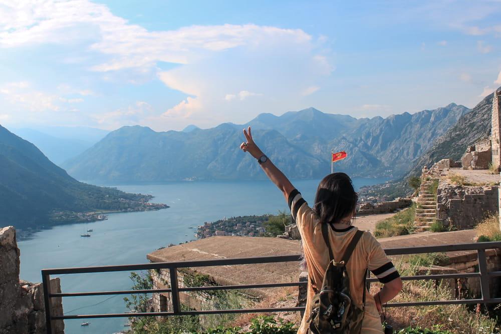 Marjorie no topo da muralha de Kotor, fazendo o sinal da paz. Vista, ao fundo, dos fiordes do litoral de Montenegro com o Forte de São João ao lado.