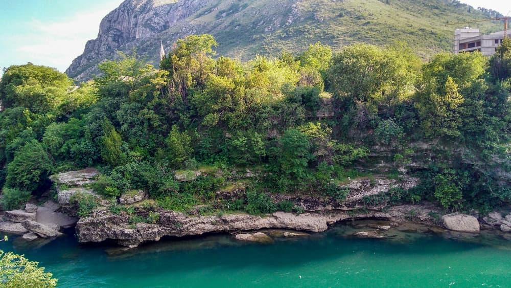 Roteiro Bálcãs: Paisagem de uma das estradas indo para Mostar, com um rio super cristalino e de cor azul turquesa, além das montanhas cobertas de verde ao fundo.