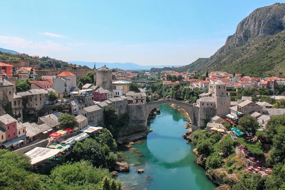 Roteiro Bálcãs: Vista do alto de um dia em Mostar, com a ponte otomana sobre o rio Neretva, que tem águas cristalinas e turquesa.