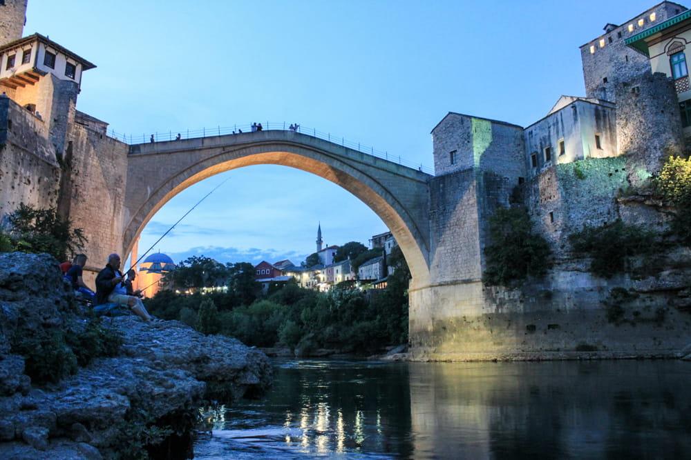 Roteiro Bálcãs: Stari Most, uma ponte famosa de Mostar vista por baixo, ao anoitecer, com luzes a iluminando e algumas pessoas pescando no rio.