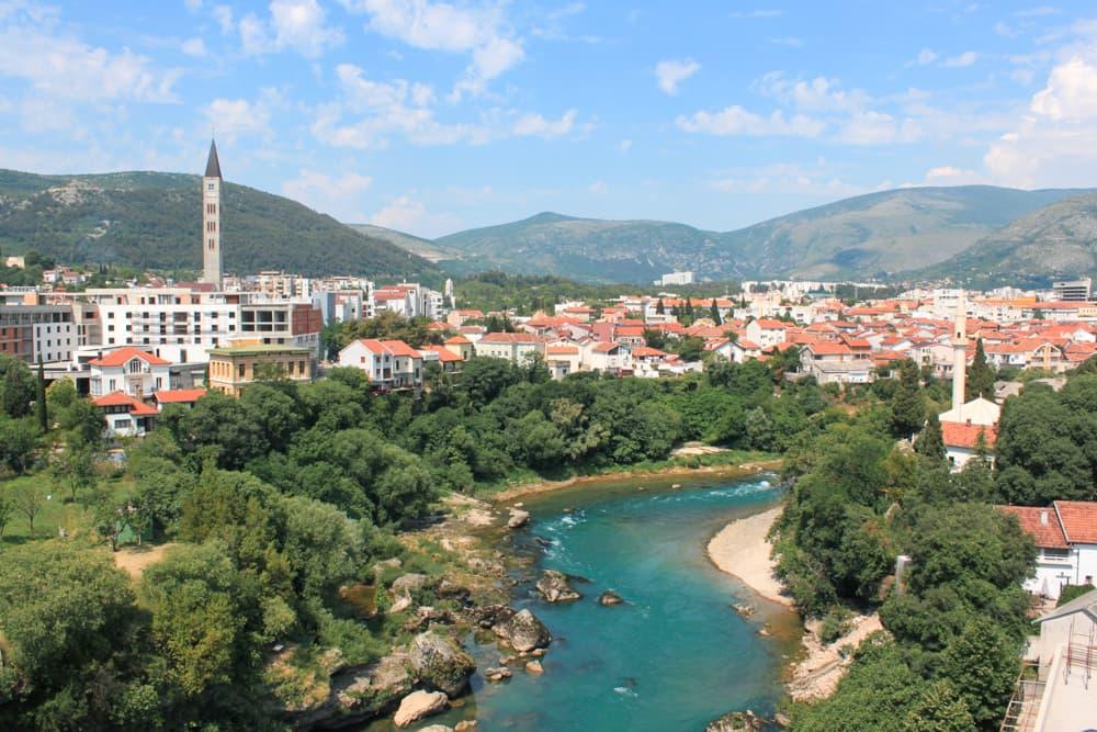 Roteiro Bálcãs: Vista do Rio Neretva, em Mostar, em um dia de sol, com suas águas turquesa chamando a atenção. A presença de árvores em volta do Rio e de casas com o seus telhadinhos laranjas compõem a foto.