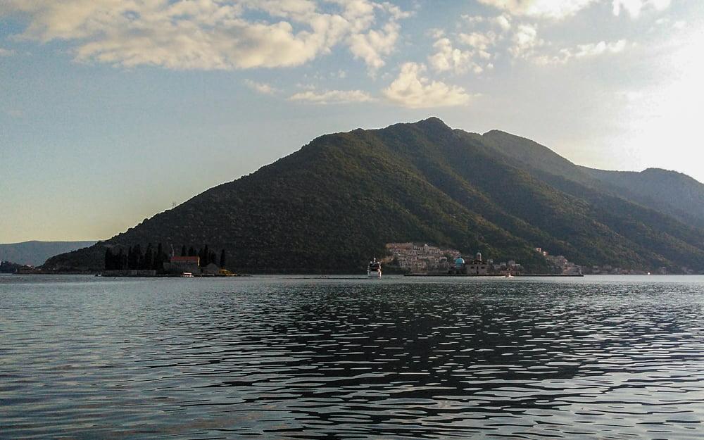Mar que banha uma das praias de Perast, à tarde, com a Ilha de São Jorge, que tem um antigo monastério beneditino, e uma cidade encrustada em uma montanha ao fundo.