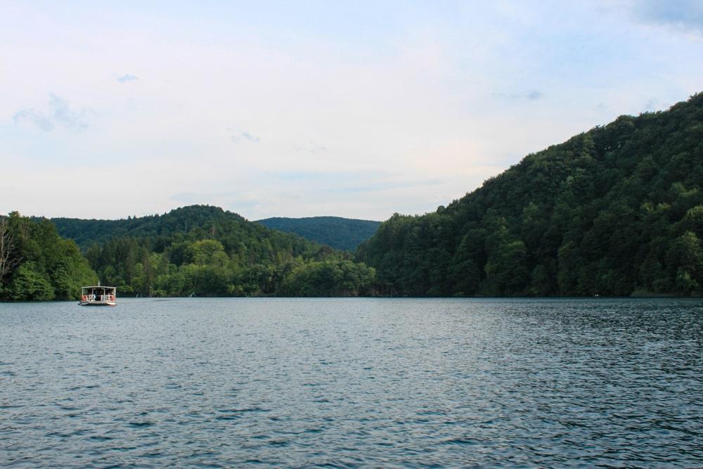 Travessia de barco, já inclusa no ingresso, por um dos lindos e cristalinos lagos de Plitvice, com vista para montanhas e árvores.