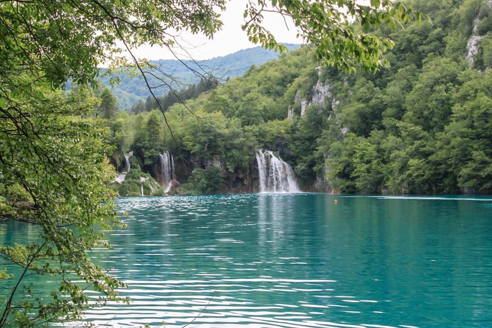 Roteiro Bálcãs: Um dos lagos cristalinos e turquesa de Plitvice, com algumas quedas d'água e muitas árvores ao fundo, iluminados pela luz do dia.