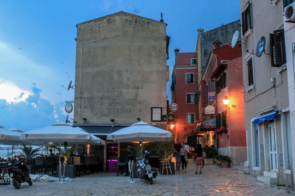 Roteiro Bálcãs: Centro de Rovinj no final da tarde, com pessoas passeando na ruazinha de pedra do lado das tendinhas dos restaurantes.