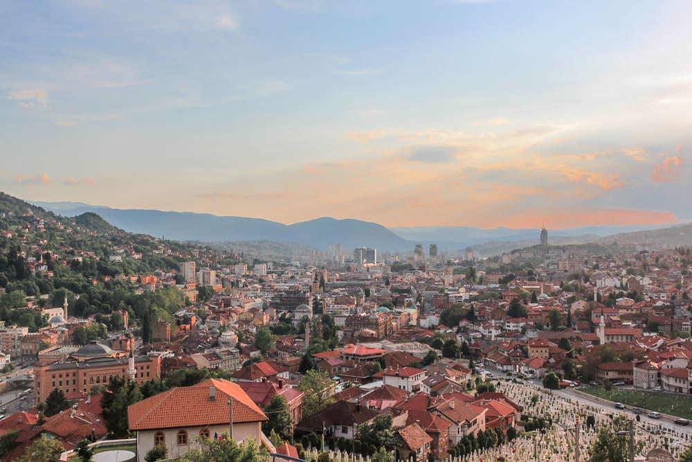 Roteiro Bálcãs: Vista do por do sol e da cidade antiga de Sarajevo na Fortaleza Amarela, com cemitérios e telhados laranjas.
