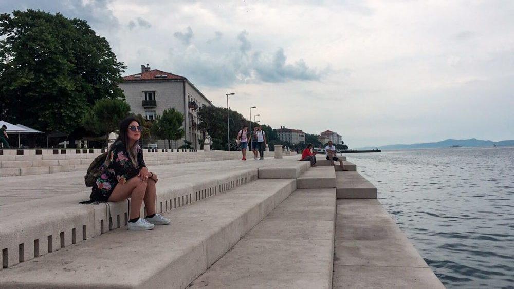 Roteiro Bálcãs: Órgão do Mar ao final da tarde na cidade de Zadar. Marjorie e outras pessoas sentadas esperando pelo pôr do sol mais lindo do mundo.