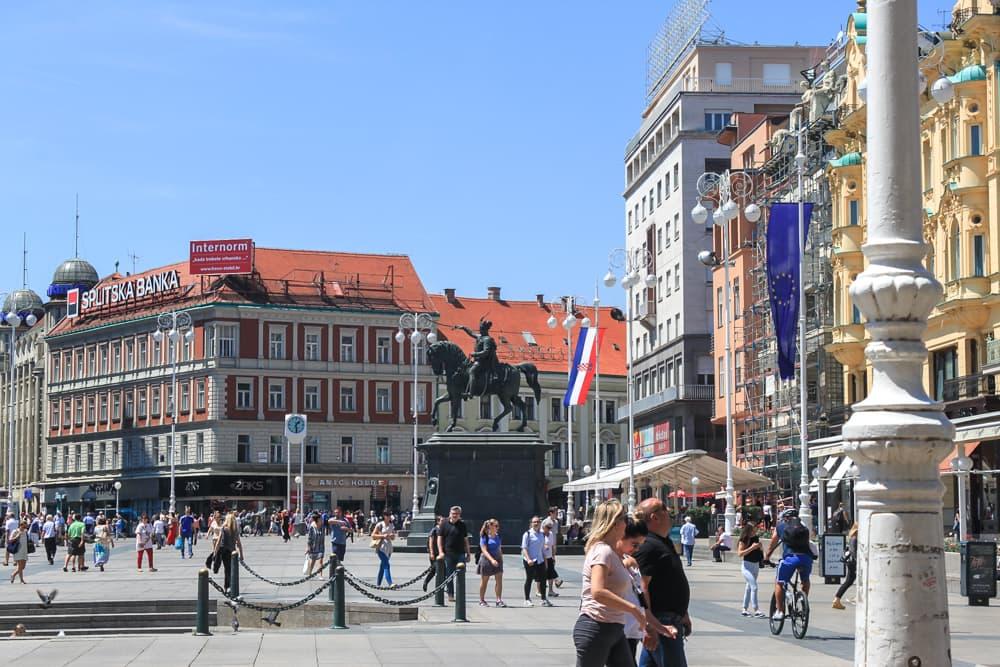 Roteiro Bálcãs: Praça Central de Zagreb durante o dia, com moviemento de pessoas e a estátua do cavalo ao fundo.