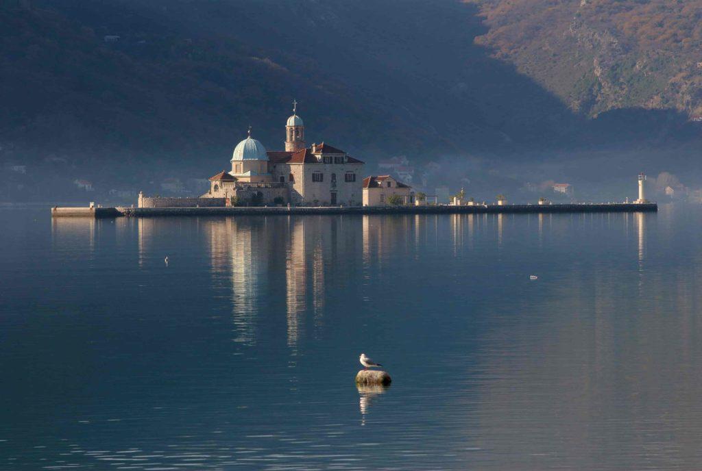 Ilha de Nossa Senhora das Rochas com a sua Igreja, no calmo mar de Perast, Montenegro.