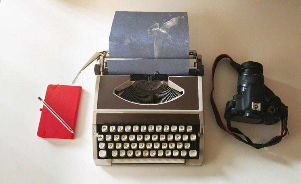 Máquina de escrever ao centro, com uma câmera DSLR à direita e um caderno de anotações vermelho à esquerda.