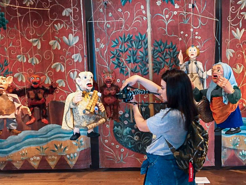 Marjorie tirando foto de um boneco de fantoche em um colorido teatro de bonecos, na cidade de Óbidos