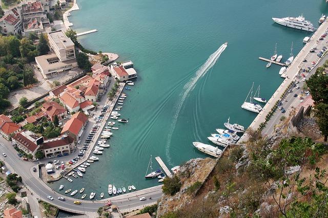 Vista aérea do porto de Kotor, com barcos ancorados e estrada com carros