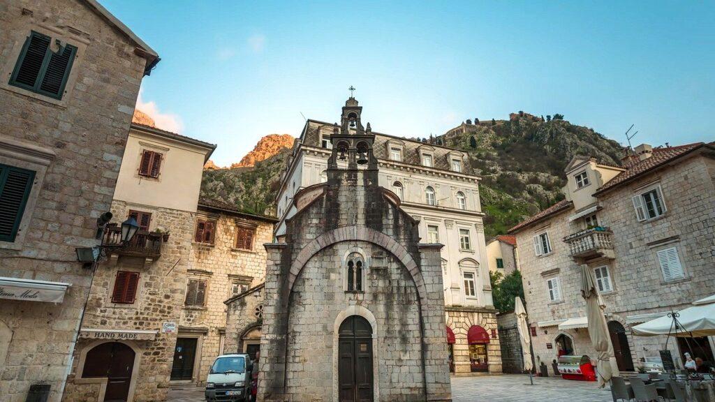 Construções do centro da cidade medieval de Kotor, com a sua muralha ao fundo