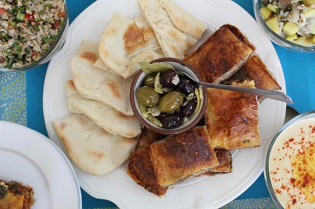 Uma massa fina de Burek, uma das comidas típicas de Sarajevo, servida com pão pita, azeitona verde e azeitona preta.