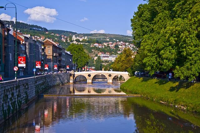 Dia de sol em Sarajevo com vista para Ponte Latina cercada por árvores e sobre o Rio Miljacka, com uma montanha cheia de casas ao fundo.