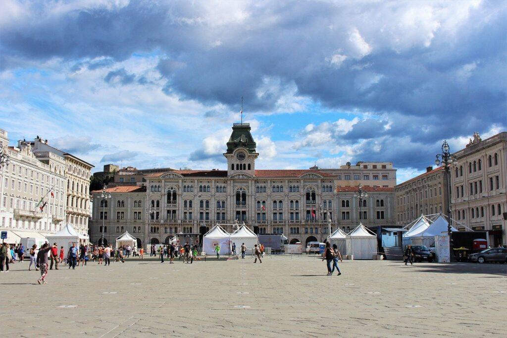 Foto da Piazza Unità d'Italia, a mais importante de Trieste, com o prédio da Câmara Municipal ao fundo durante o dia, com várias pessoas passeando.