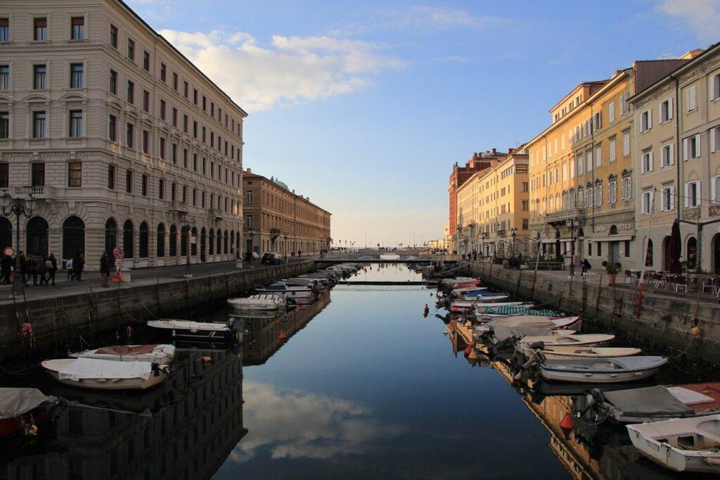 O céu do final da tarde refletindo no Grande Canal de Trieste, que está cheio de barcos ancorados e com suas margens cheias de prédios.