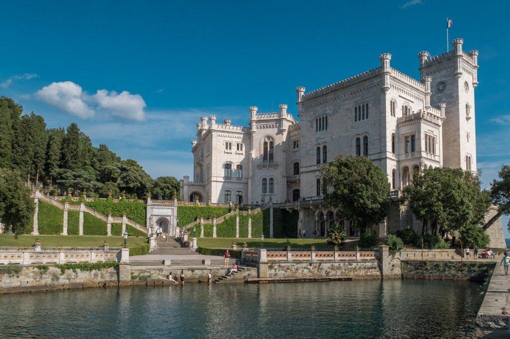 Parte de trás do Castelo de Miramare, com um portão que fica no meio de uma parede de jardim vertical. O Castelo tem uma área muito verde e cheia de árvores, com uma arquitetura linda, por isso é um dos mais visitados de Trieste.
