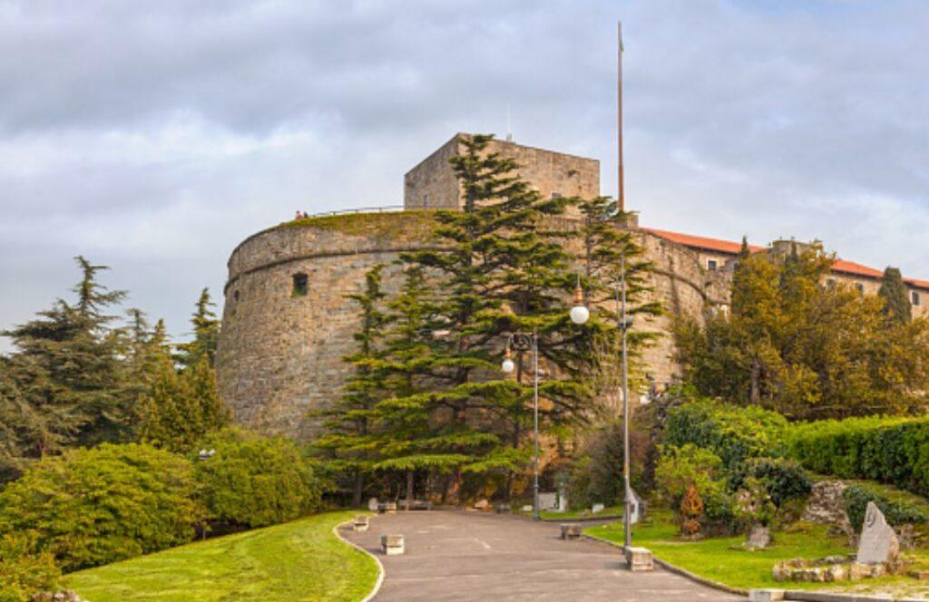 Parte do Castelo de das Muralhas de San Giusto no meio de muita vegetação e pinheiros.