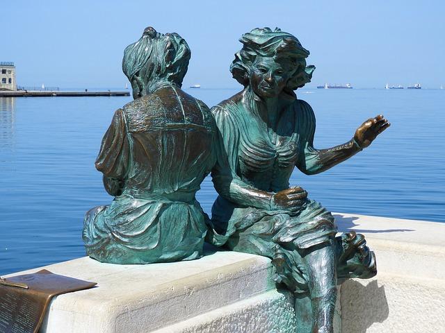 Estátua da Le Ragazze di Trieste, que fica localizada na região do Molo Audace, com o mar adriático e vários barcos no fundo.