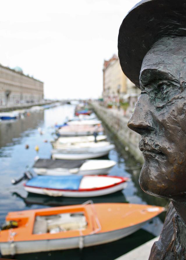 Parte da estátua de James Joyce, que morou um tempo em Trieste, que fica na Ponte Rosso, com o Grande Canal cheio de barcos ancorados de fundo.