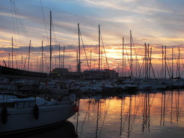 Pôr do sol refletindo nas águas adriáticas do Molo Audace em Trieste, com vários barcos e lanchas brancas ancorados.