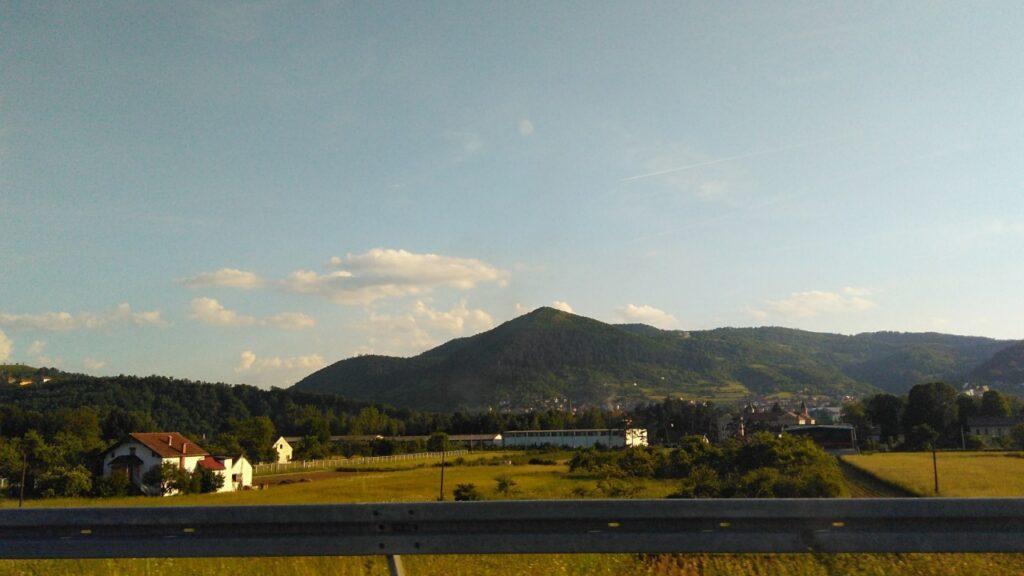 Vista de uma estrada da Bósnia, com pastos e montanhas verdes ao fundo