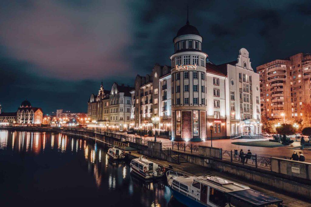 O Kaiserhof Hotel, que fica localizado na Vila dos Pescadores em Kaliningrado, na parte da noite com a sua fachada e a de todos os prédios em volta iluminadas e refletindo nas águas da margem do rio pregolia .