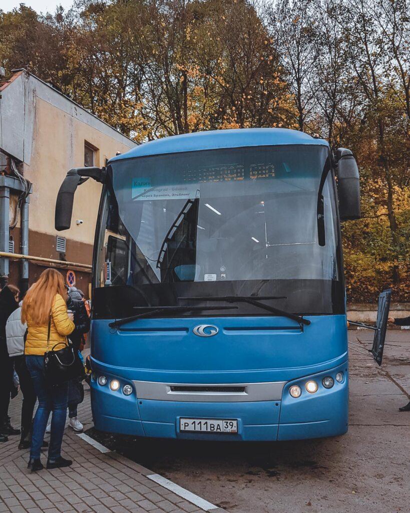 Pessoas embarcando em um ônibus azul, na rodoviária de Gdańsk, em direção à Kaliningrado