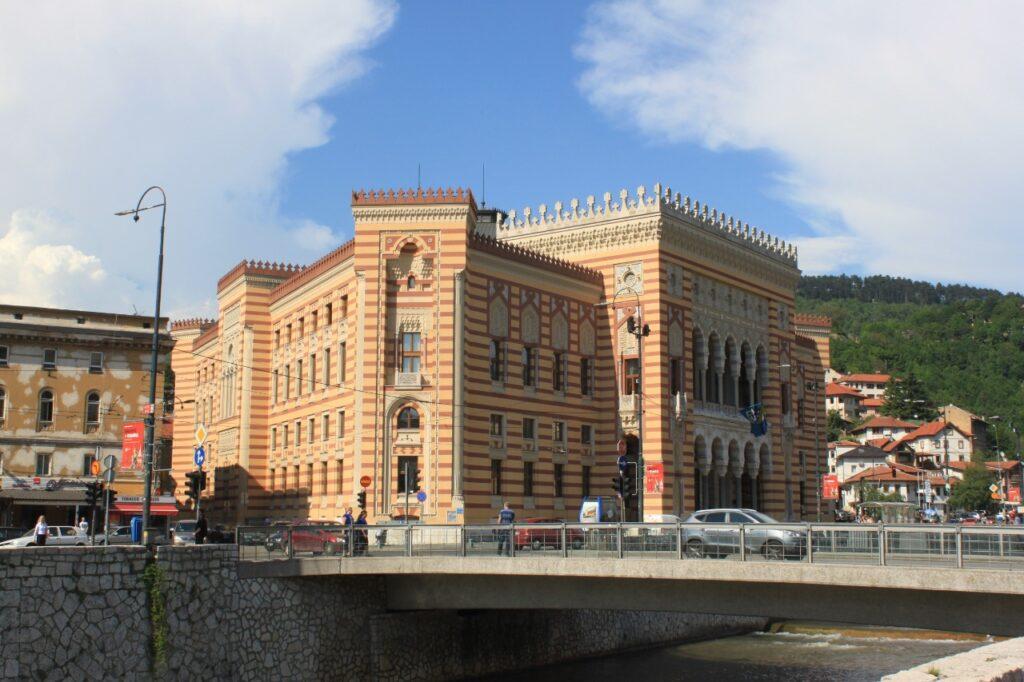 Prédio da prefeitura colorido listrado nas margens do rio em Sarajevo.