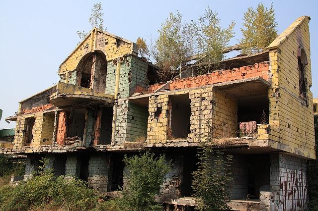 casa com paredes cheias de marcas de tiros e em escombros