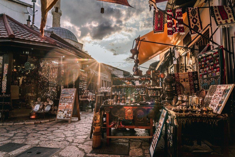 Vários produtos de cobre e tapeçarias em frente às lojas da Baščaršija