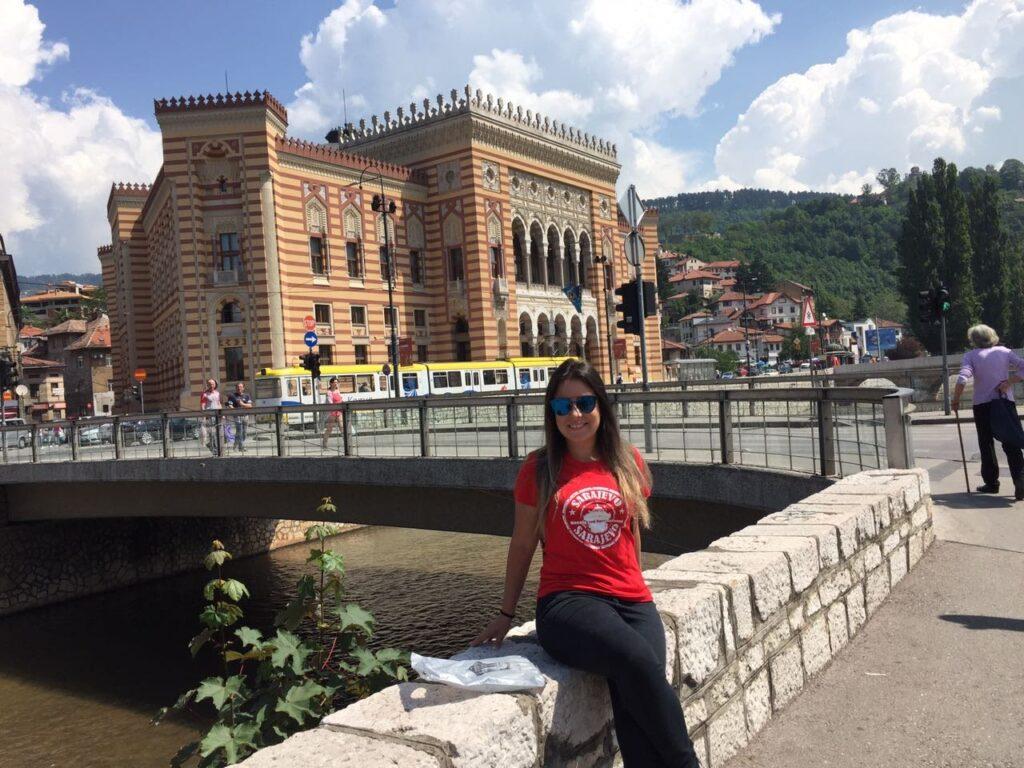 Prédio da prefeitura colorido listrado nas margens do rio em Sarajevo, com Marjorie à frente