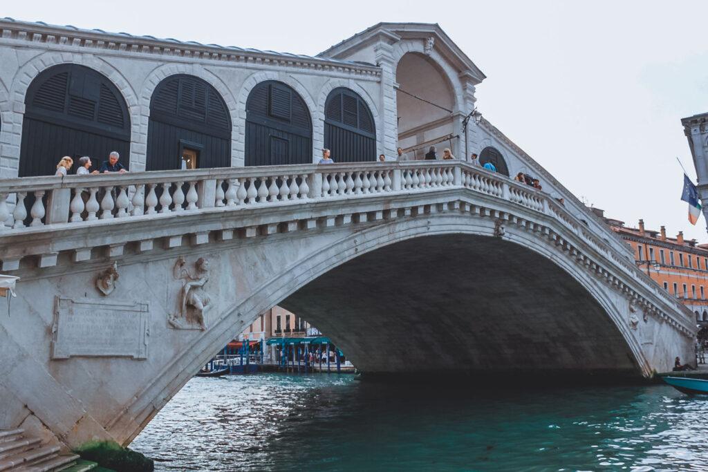 Ponte Rialto vista de baixo, com o Grand Canal de Veneza e movimento de turistas